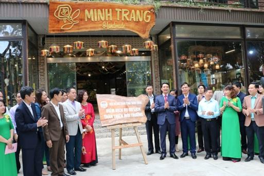 Các đại biểu gắn biển điểm dịch vụ du lịch thân thiện với môi trường tại cửa hàng Thêu Minh Trang.